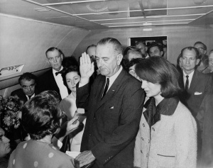 Standing in her (now) iconic and (forever) stained Chanel suit, Jackie looks on as Lyndon Johnson is sworn in on Air Force One.